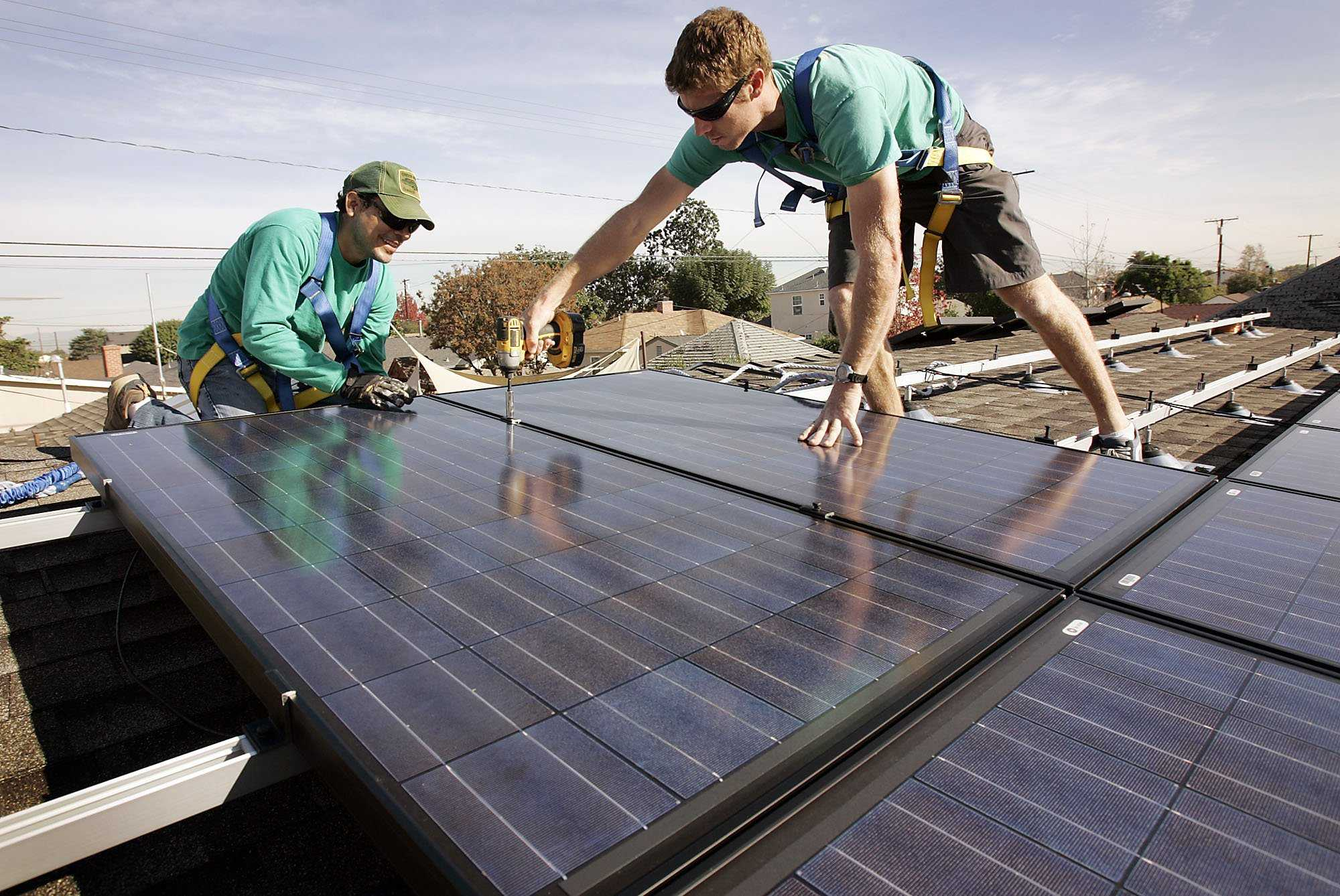 Joey Ramirez, left, and Taran Stone with SolarCity install solar modules on the roof of a Long Beach, Calif., home. Florida