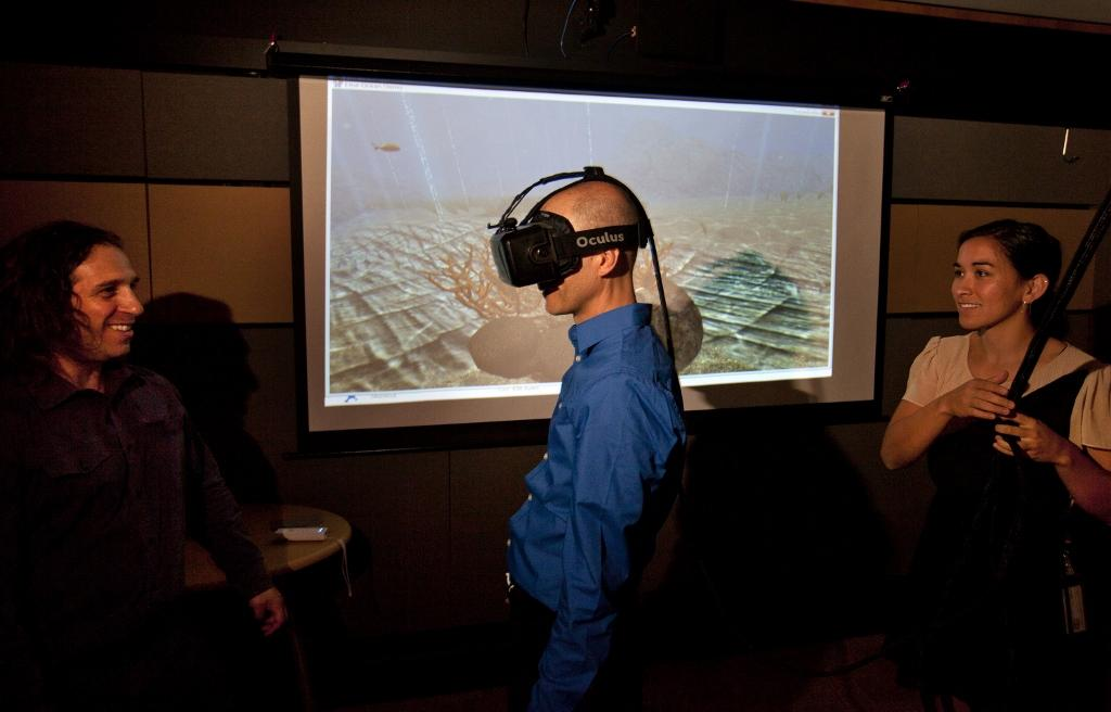 San Jose Mercury News reporter Troy Wolverton uses an Oculus Rift virtual reality system as founding director Jeremy Bailenson, left, and researcher Elise Ogle look on at Stanford University's Virtual Human Interaction Lab in Palo Alto, Calif., on June 24, 2015. Consumers will have their pick of four high-profile virtual systems from major electronics companies, including Facebook's Oculus Rift. (Patrick Tehan/Bay Area News Group/TNS)