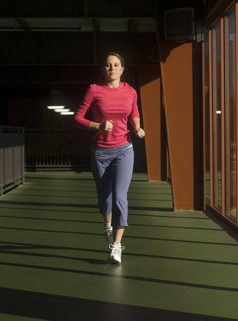 A woman runs by the windows at Golds Gym in Lexington, Kentucky.