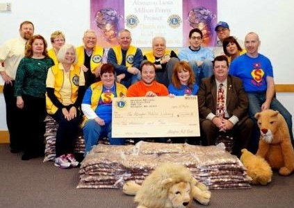 Lion's Club Members sitting on and around the pennies they raised for the Abington Public Library