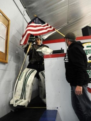 Mike Morse takes the ice as Bob Morse holds Old Glory above him.   (Photo Courtesy Marc Vasconcellos/The Enterprise)