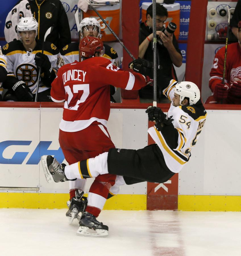 The Detroit Red Wings' Kyle Quincey, left, puts a hard check on the Boston Bruins' Adam McQuaid in the second period at Joe Louis Arena in Detroit on Thursday, Oct. 9, 2014.