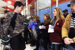 From left, Abington High School's Jacke Morse gives Erin Vasselian, the wife of Daniel, a bouquet of flowers, Karen Vasselian (mom of Daniel), also got flowers. Abington High School hockey team honored United States Marine Sgt. Daniel Vasselian before their hockey game on Saturday, Jan. 10, 2015. The game was against rival Rockland High School.  The Abington High School hockey team wore camouflage jerseys and Danny's brother Joe did the ceremonial puck drop before the game.  Also  Massachusetts state police Sgt. Tim Grant sang the National Anthem.   (Marc Vasconcellos/The Enterprise)