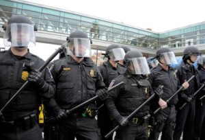 Police dressed in riot gear hold their line on Pratt Street near Howard in Baltimore on Saturday, April 25, 2015, as protests continue in the wake of Freddie Gray's death while in police custody.