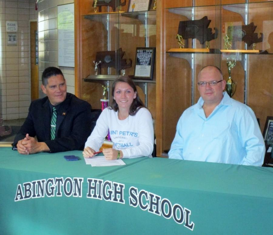 Katie Donovan signs her letter of intent to St. Paul's University with Abington coach Ernie Ortega to her right and her father John Donovan to her left.