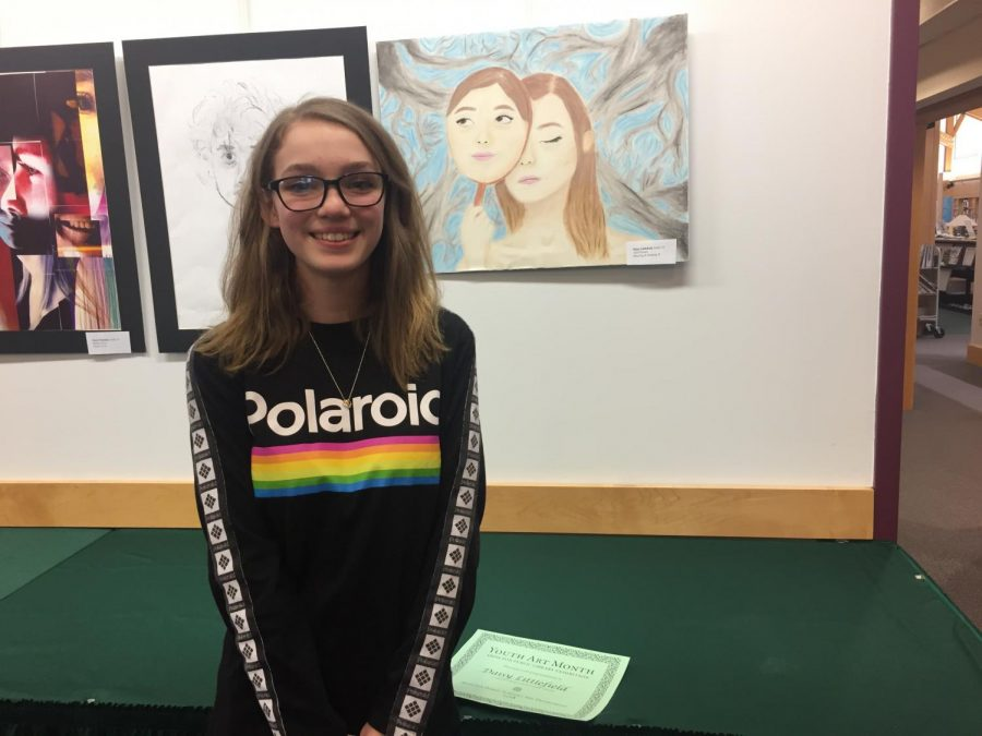 Daisy Littlefield in front of one of her drawings