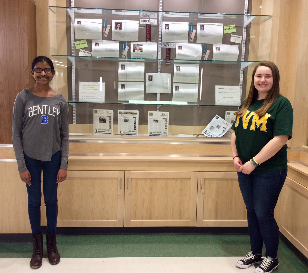 Nivetha Aravindan and Allison Dennehy in front of the Green Wave Gazette display