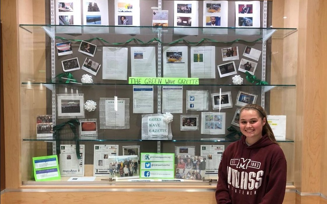Abby Joyce, Staff Writer and PR Manager of the Green Wave Gazette, in front of the display she created