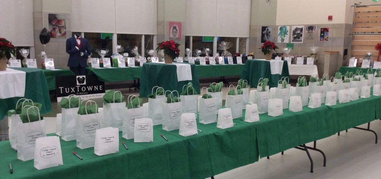 The Junior Class Auction of 2018 had many silent auction stations, such as this one. Auction-goers could put tickets in for the 50/50 raffle (shown in front), bid on silent auction items or participate in the live auction.