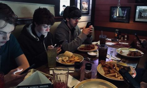 Abington students gather together while on their phones at a local restaurant after school on the half day Friday, Jan. 25. Left to right are Sean Moran