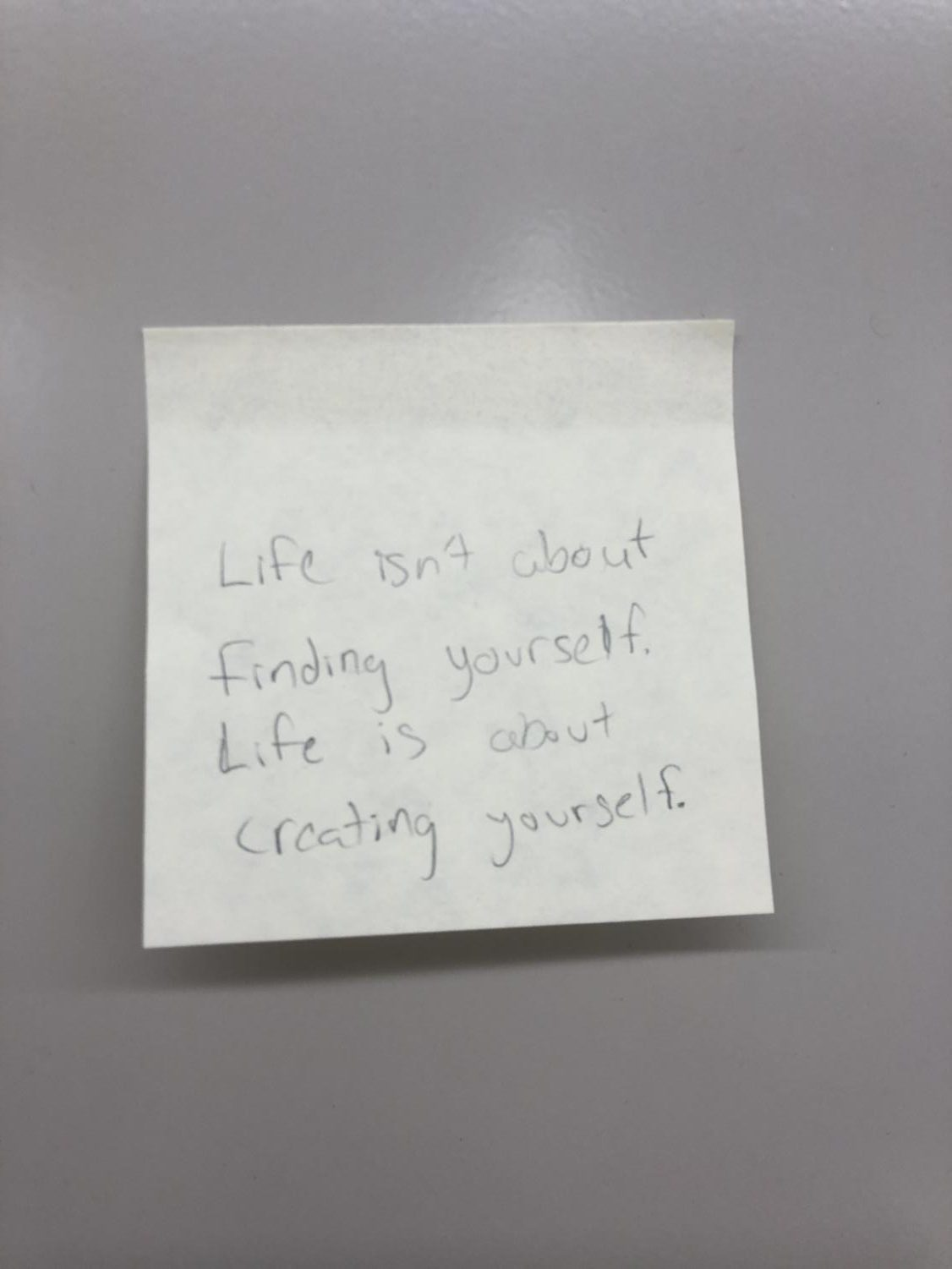 A+sticky+note+with+the+quote+%22Life+isn%27t+about+finding+yourself.+Life+is+about+creating+yourself.%22