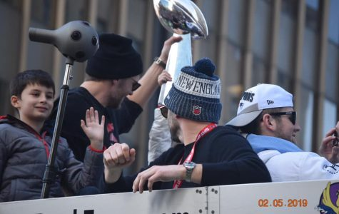 Benjamin Brady smiles and waves to the crowds in Boston while father and Patriots quarterback Tom Brady (with trophy) hoists one of NE's six championship trophies on Tuesday, February 5, 2019.