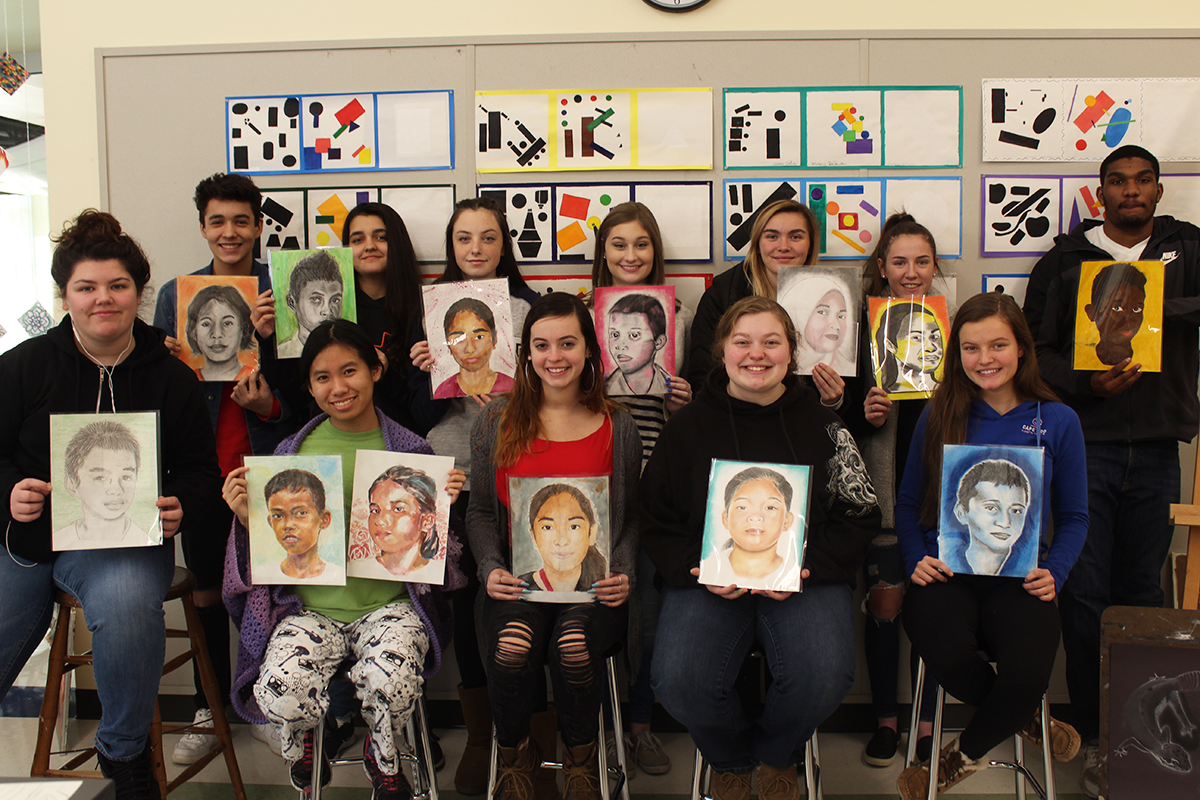This+is+the+third+year+that+Abington+High+School+teacher+Mrs.+Michelle+Poirier%27s+art+students+have+painted+portraits+of+children+for+The+Memory+Project.+Seated+left+to+right+are+seniors+Victoria+Stockbridge%2C+Julia+Do%2C+Jenna+Galvin%2C+and+Hailee+McClafferty%3B+and+junior+Emmalee+Ezzell.+Standing+left+to+right+are+sophomores+Luciano+DiSilva%2C+Sthefany+DePaula%2C+and+Faith+Kramer%3B+seniors+Brooke+Pettenati%2C+Jane+Clark%2C+and+Makayla+Zulon%3B+and+junior+Jarae+Cole.
