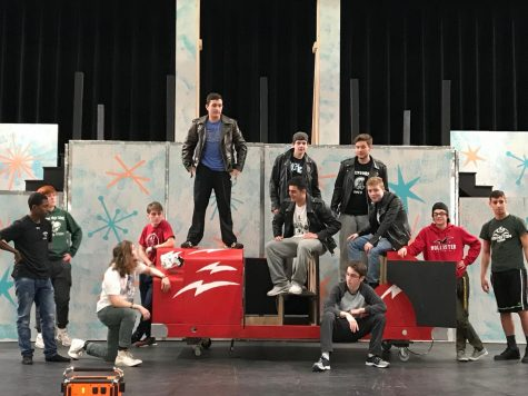 Abington High School junior Connor Saccoach (standing on the car), who plays Kenickie, sings Greased Lightning in a rehearsal held in the auditorium last week. Surrounding Saccoach (on the left) is senior Josiah Rosa, junior Reid Norton, junior Kyle DeGrenier (kneeling), and junior Bobby Molloy. On the right of Saccoach is sophomore Brendan Remillard and senior Jason Kinniburgh (both standing in rear); senior Dylan Magararu, freshman Will Charbonnier and sophomore Brian Tolan (both sitting on the car); junior David Collins, and junior Yaz Zaidan. The AHS Drama Club will present Grease on March 14 and 15 at 7:30 p.m. and March 16 at 2 p.m.