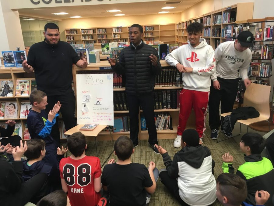 Seniors (left to right) Adrian Mendez, Josiah Rosa, Brian Quintero, and Joey Godfrey, teaching their younger fifth grade peers about yoga and its benefits on April 4, 2019 in the Abington Middle-High School Library.