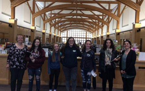 Ms. Grimmett, Jacklyne Goduti, Olivia Coy, Gretchen Mueller, Maria Wood, Ms. Milloshi, and Ms. Roberts at the circulation desk in the Abington Public Library