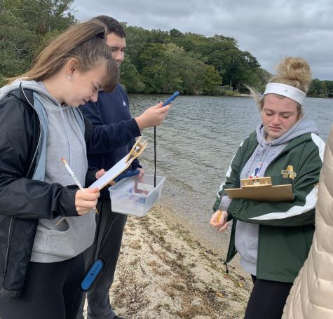 Abington High School seniors Kylie Roberts (left), Connor Whidden, and Mikayla Littman (right) test the wind speed at Mashpee Pond, Cape Cod, on an October 3, 2019 Environmental Science class field trip.