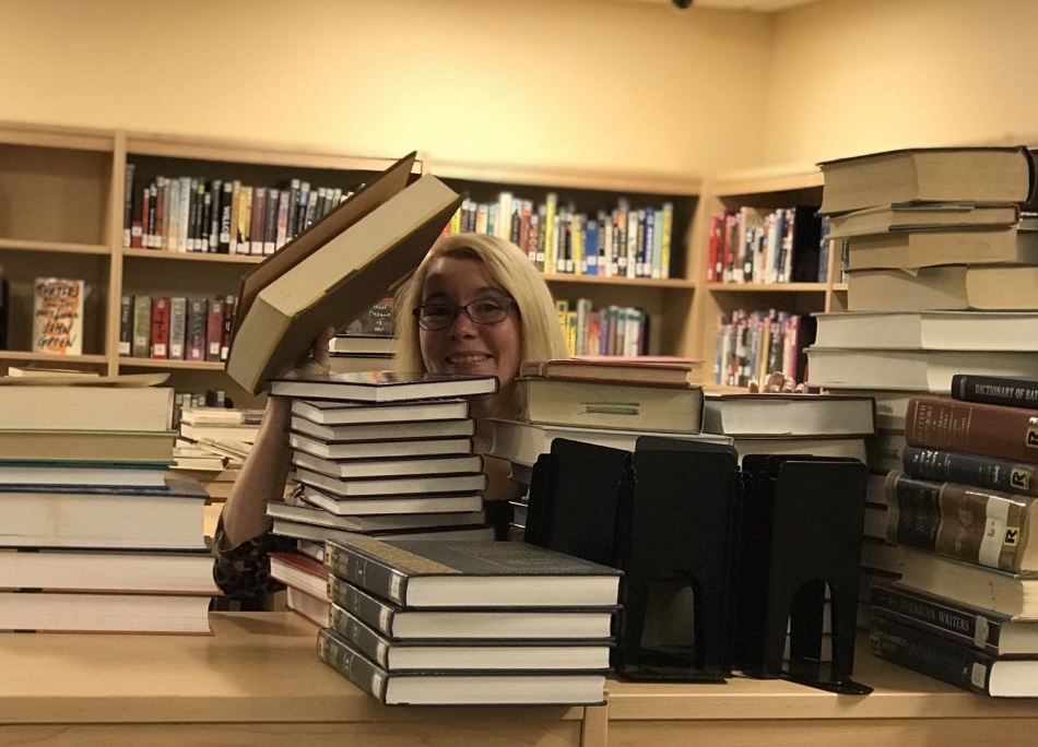 Mrs. London working very hard to reorganize the library and make it easier for students to find the books they need in the Middle-High School Library in October of 2019.