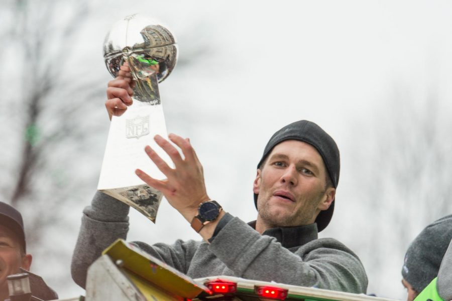Patriots quarterback Tom Brady lifts the trophy as he rides one of the duck boats during the Super Bowl LI victory parade in Boston on Tuesday, February 7, 2017