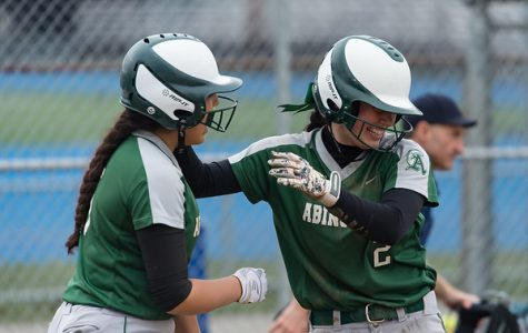 Corin Mahan (L) and Lauren Keleher (R), both members of Abington High School's Class of 2020, celebrate after an away 9-3 win over Braintree High School on May 4, 2019