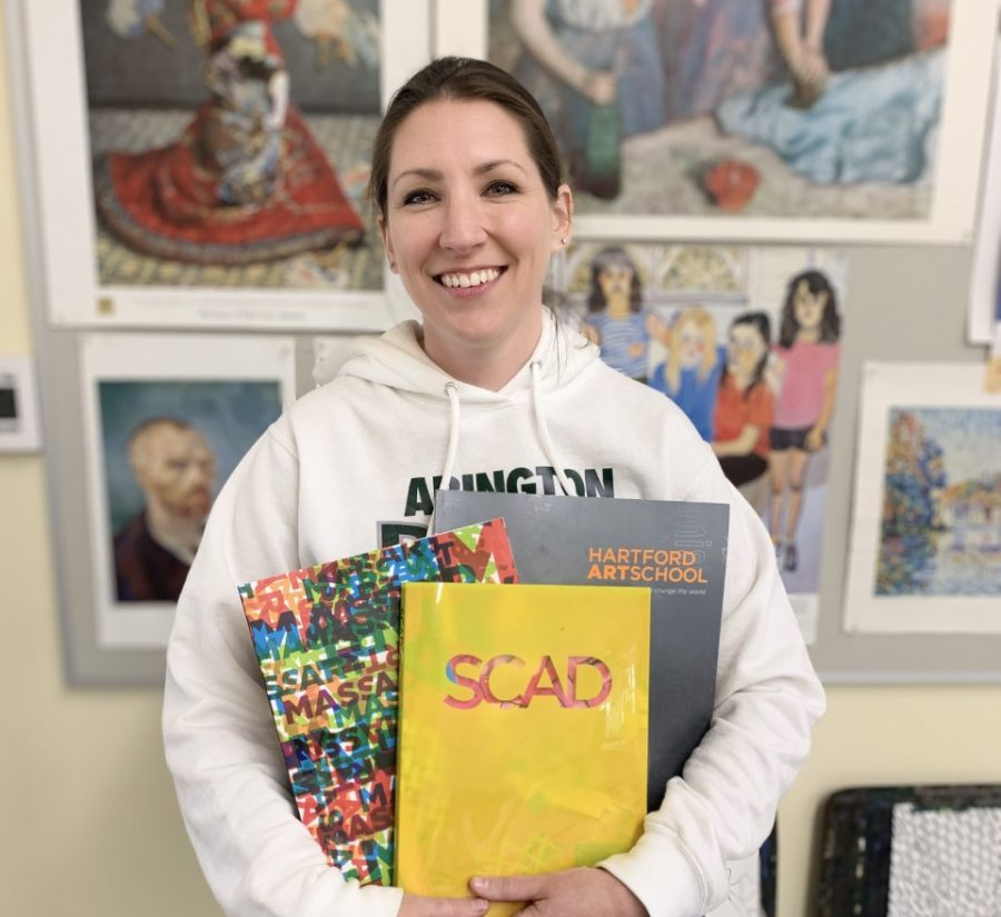 Ms. Michelle Poirier holds some of the course catalogs from colleges she invites to her art classroom at Abington High School. Recently several art colleges came to speak to her students about a career in art.