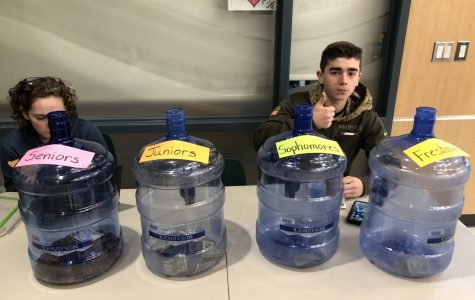 Abington High School freshman Amaya Turner and junior Jack Clifford, members of the Green Wave Gazette, sit with the Penny War containers in the cafeteria on Tuesday, February 11, 2020. They are two of about a dozen students who helped in the fundraiser.
