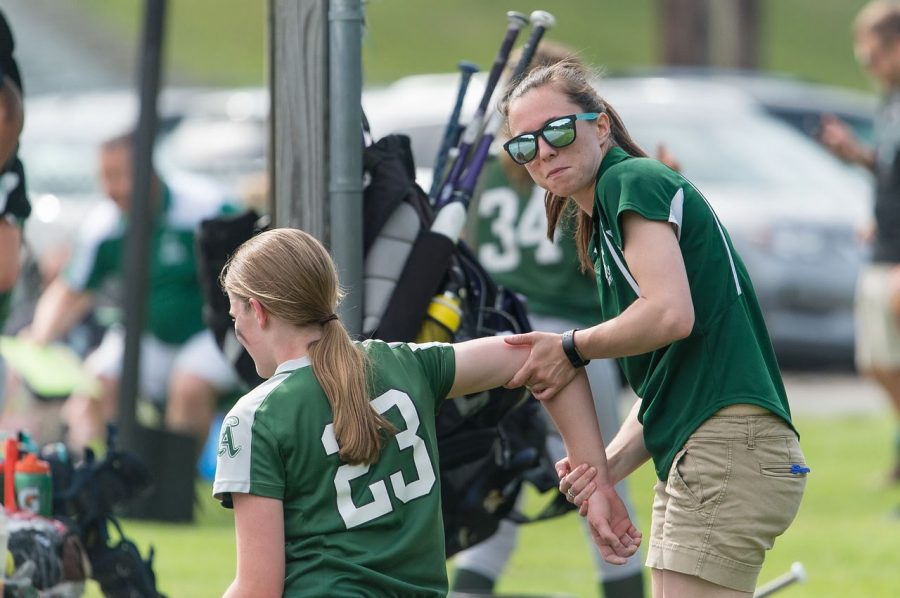 Abingtons Athletic Trainer Ms. Alicia Reid (right) stretches the shoulder of softball player Victoria Seppala (Class of 2021).