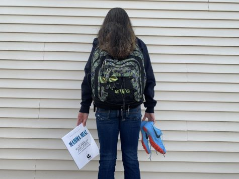 "Abington High School sophomore Maria Wood holds a ""Mamma Mia!"" script, her backpack, and running spikes on March 14, 2020 as representations of cancellations due to the COVID-19 pandemic"