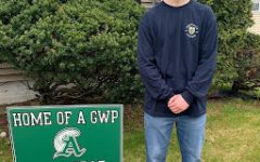 Bubba Gendreau stands in front of a Green Wave Pride sign that the Class of 2020 advisors placed on student lawns. Gendreau has committed to attending Merrimack College this fall.