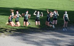 The Abington High School Girls Cross Country team leap for joy at their meet against Middleborough on October 21, 2020.