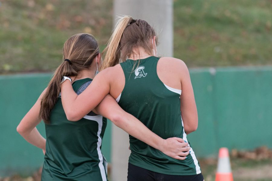 Maddi Carini supports an injured Hannah Tirrell as they make their way to the finish line at their meet against Randolph on November 20, 2020.