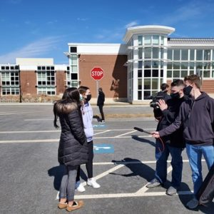 Abington High Schools seniors Aaron Johnson (right front) and Matt Lyons (right rear) of the student newspaper The Green Wave Gazette interview fellow seniors Erin Doherty (front left) and Lily Bonner on March 16, 2021 in front of Abington High School after a fire alarm sounded and the school was evacuated.