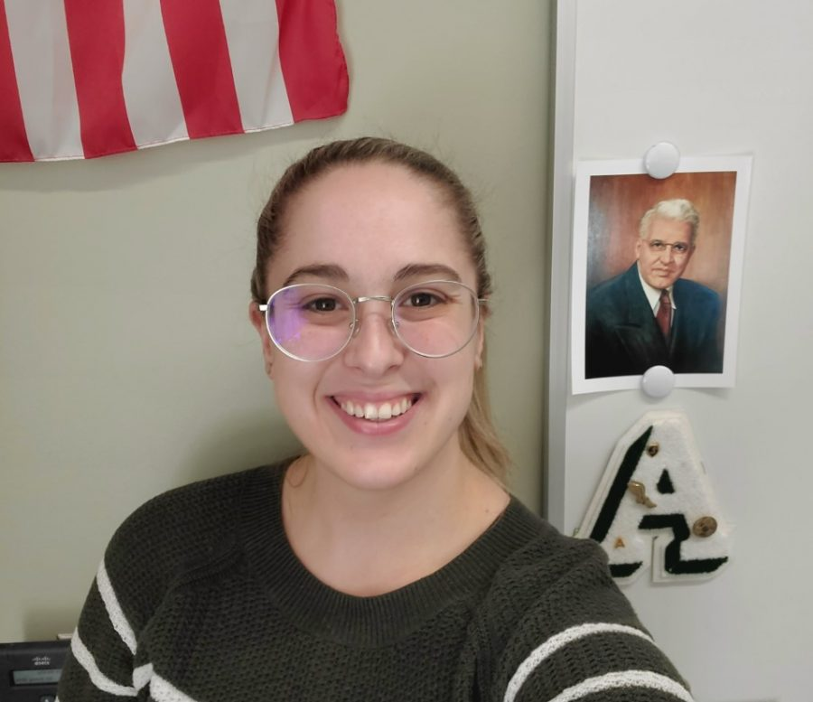 Ms. Megan Tomlin in her English classroom at Abington High School on March 9, 2021. Tomlin stands in front of a photo of Charles M. Frolio, whose name was on the former middle school in town. Tomlin, and AHS alumna, also taught at and attended the Frolio Middle School.