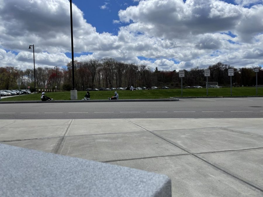 Sitting on the grassy area outside of school, students in Ms. Tomlin's AP Literature and Composition class work in groups after taking a break at Abington High School on April 30, 2021.