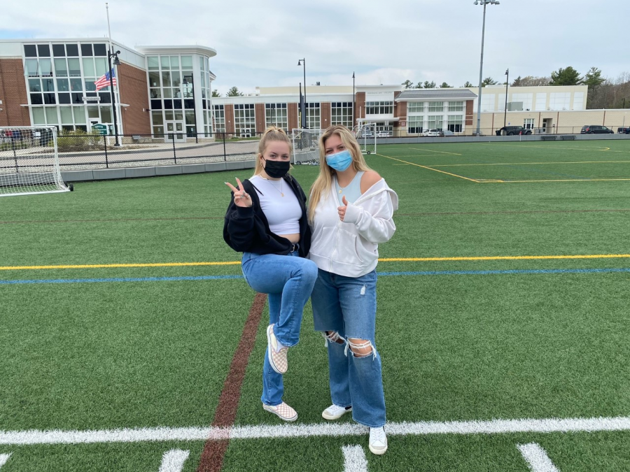 Seniors, Ella Hughes (left) and Mackenzie Cahill (right) in their 2000's outfits enjoying the sun on the turf at Abington High School on Wednesday April 28, 2021.
