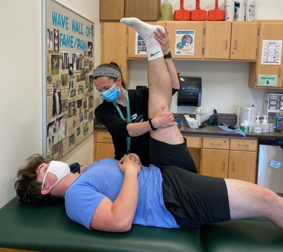 Abington High School's  Athletic Trainer Alicia Reid attends to junior Shea McClellan for a physical therapy session at the high school. McClellan endured a medial collateral ligament  (MCL) tear at a football scrimmage in  March.