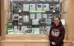 Senior Abigail Joyce poses in front of the display case containing some of the Green Wave Gazettes work in the upstairs rotunda in 2019.