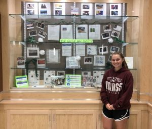Senior Abigail Joyce poses in front of the display case containing some of the Green Wave Gazette's work in the upstairs rotunda in 2019.