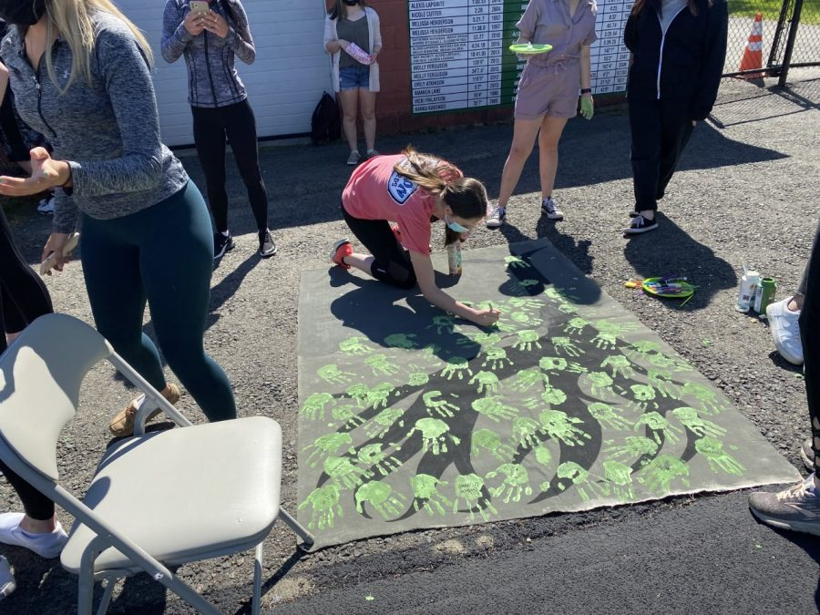 Senior class secretary Carly Mentis holds a hand painting station during the senior event held on Friday, May 14, 2021 at Reilly Field.